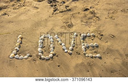 The Word Love Is Laid Out With Shells On The Sand.