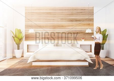 Thoughtful Blonde Woman Standing In Luxury Master Bedroom With White And Wooden Walls, Comfortable K