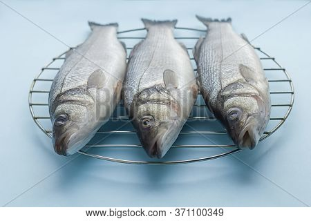 Fresh Raw Sea Bass Fish On The Grill On A Blue Background. Proper Nutrition, Mediterranean Diet.