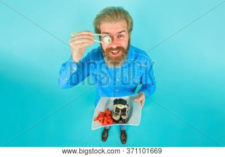 Seafood. Man Eating Sushi. Man Hold Piece Sushiroll In Front Of Eye. Man With Sushi On Chopstick. Su