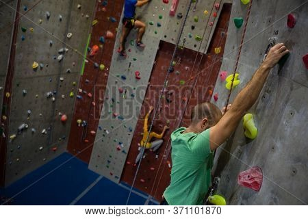 Dedicated athelets climbing wall in health club