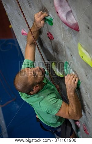 High angle view of confident male athlete climbing wall in health club