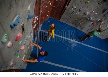 High angle view of athletes examining climbing wall in health club