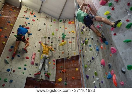 Low angle view of athletes rock climbing in health club