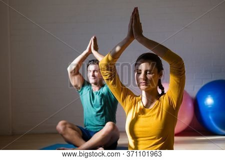 People meditating in prayer position at health club