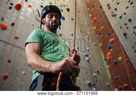 Low angle view of male athlete tying rope while standing in health club