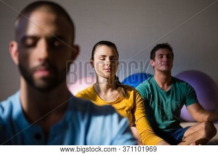 Male instructor with students meditating in lotus position at health club