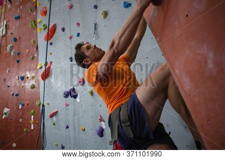 Low angle view of confident male athlete rock climbing in health club