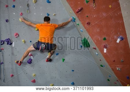 Rear view of male athlete rock climbing in health club