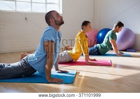 Male instructor with students practicing cobra pose in health club