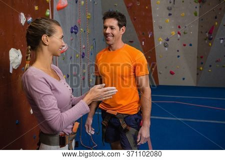 Side view of female athlete talking to male trainer at health club