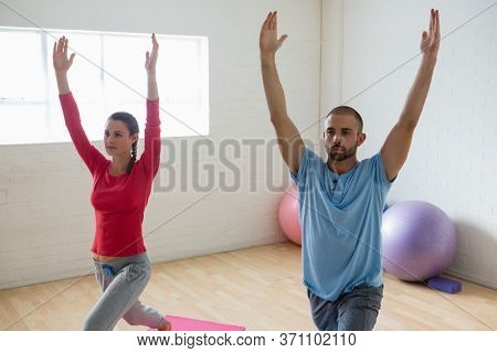 Male instructor with student practicing warrior 1 pose in yoga studio