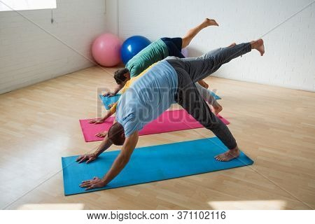 Male instructor with students practicing downward facing dog pose with feet up at health club
