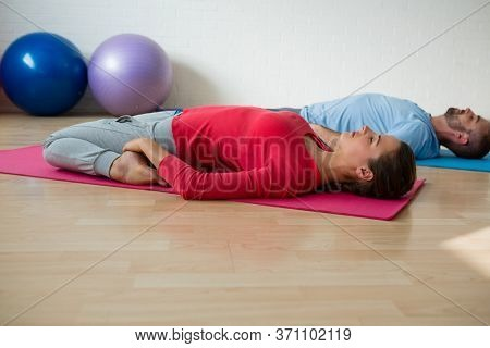 Instructor with student practicing reclined hero pose in yoga studio