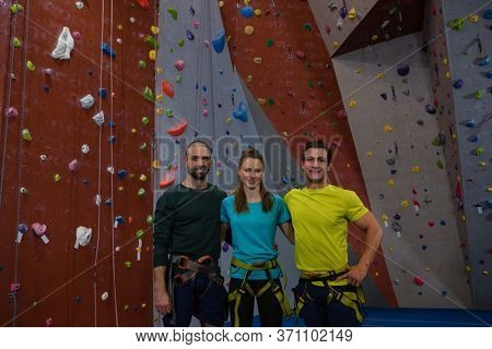Portrait of confident athletes standing by climbing wall in health club