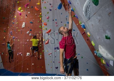 Dedicated athletes and trainer climbing wall in fitness club