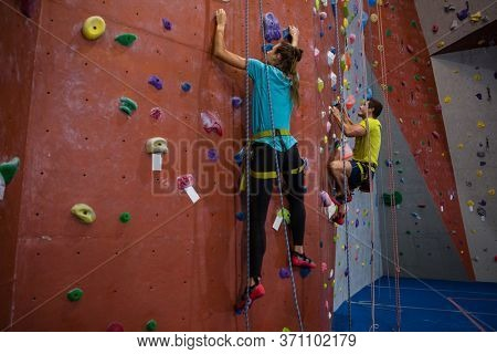 Dedicated athletes climbing wall in heath club
