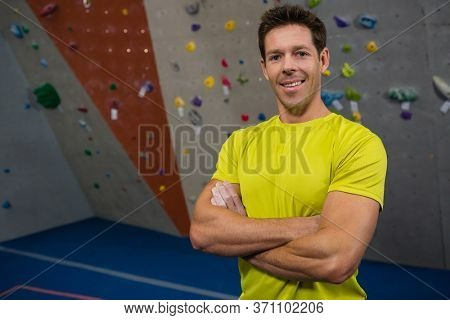 Portrait of smiling athlete with arms crossed standing in health club