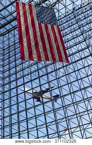 A commercial aircraft takes off from an international airport with an American flag in the foreground