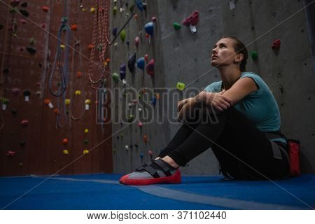 Thoughtful athlete looking up while relaxing in health club