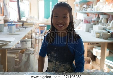 Portrait of happy girl standing at worktop in pottery workshop