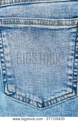 Close-up Pocket Of Denim Blue Fabric With Yellow Seams. Fashionable Rough Jeans. Vertical Top View.