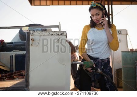 Woman talking on mobile phone while filling petrol in car at petrol pump