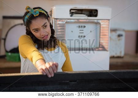 Thoughtful woman filling petrol in car at petrol pump