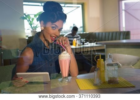 Portrait of young woman having milkshake and holding tablet looking into camera
