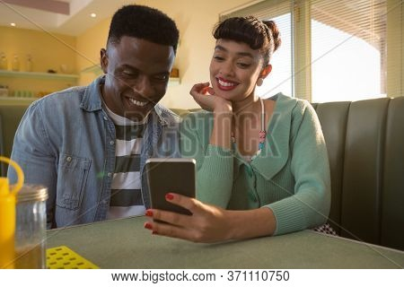 Smiling couple sitting on couch using a mobile phone in restaurant