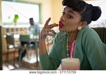 Young woman sitting on couch touching her lip in the restaurent