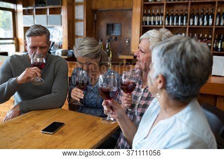 Senior friends having red wine in restaurant