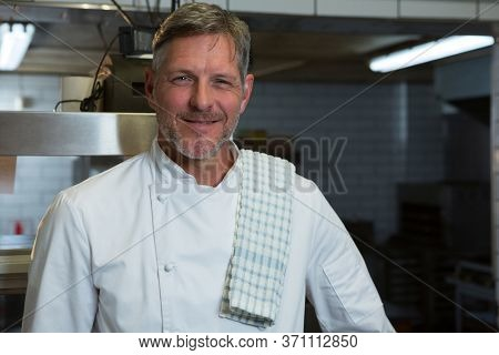 Portrait of male chef standing in commercial kitchen