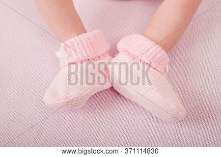 Newborn baby feet close up. Baby feet in white terry socks, baby lying on bed