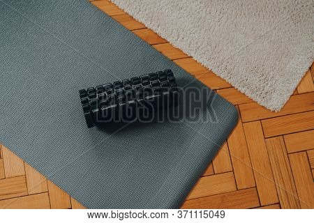 Top Down View Of A Black Foam Roller And A Fitness Mat Over Old Parquet Floor, Selective Focus.