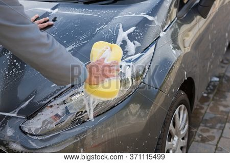 Male auto service staff washing a car bonnet with sponge