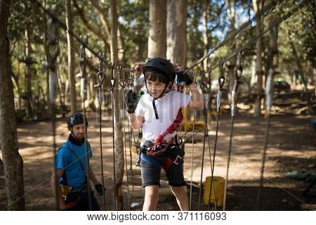 Cute boy crossing zip line in parkland on a sunny day