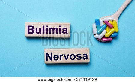 The Word Bulimia Is Written On Wooden Blocks On A Blue Background Near A Spoon With Pills. Medical C