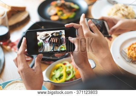 Social Media And Modern People Lifestyles. Close Up Hands Of Food Blogger Influencers Taking Picture