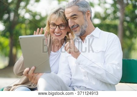 Technology Connect And Modern Elderly Lifestyles Concept. Aged Senior Couple Waving Hands Greeting G