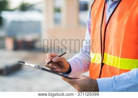 Asian Inspector Checking Structure Of New Property And Taking Note In The Clipboard For Review And F