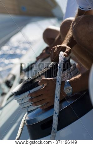 Sailor tying rope onto windlass close-up of hands