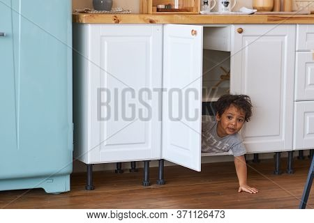 Family At Home Concept, Little Boy Playing Hide And Seek. A Happy Child Looks Out Of The Closet In T