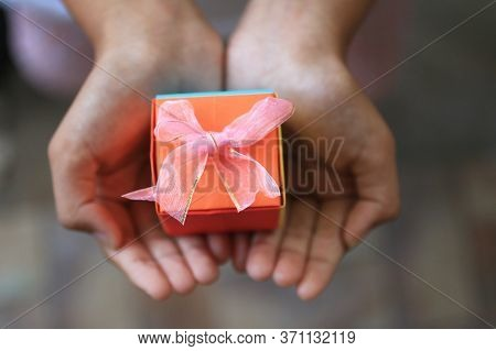 Hands Holding An Orange Gift Box. Life Is A Gift Concept. Birthday Gift. Valentine Gift. Personal Gi