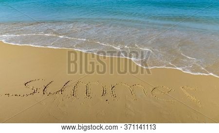 Inscription In The Sand. Sea Wave Is Approaching The Word Summer.