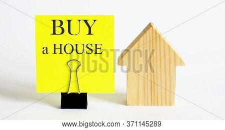 Table With Wooden Houses With The Word Buy A House . The Concept Of Rental Housing. Rent An Apartmen