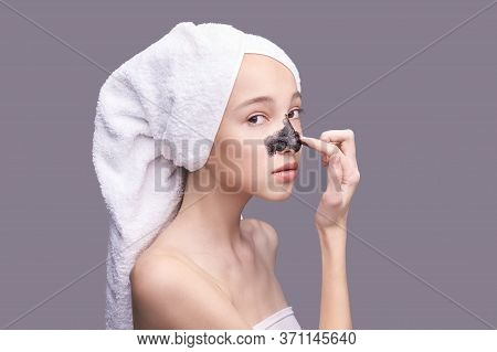 Young Girl Applying Black Face Mask. Charcoal Facial Product. Acne And Pimple Removing. Mud Coal The