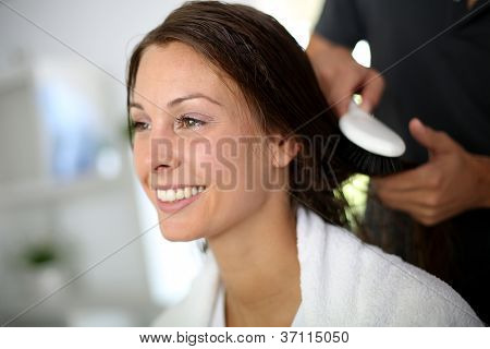 Woman having her hair brushed by hairdresser