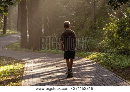 A Boy Rides A Skateboard On A Path In A City Park After Rain In The Evening Sun, Evaporation Of Mois