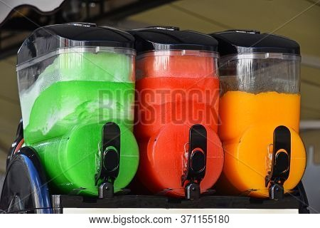Close Up Green, Red And Orange Slush Ice Granita Smoothie Drinks In Machine Canisters, Low Angle Sid